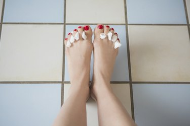 Low section of woman with tissues between painted toe nails on tiled floor