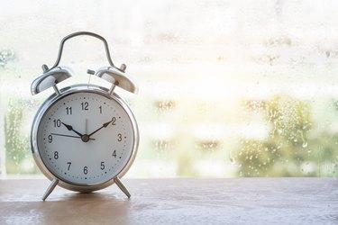 vintage  alarm clock and  classic design near window on wooden floor.
