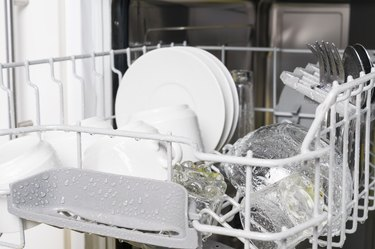 wet clean white dishes and cutlery are in the dishwasher