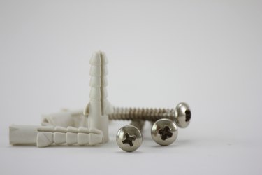 Close-Up Of Screws With Hollow Wall Anchors Over White Background