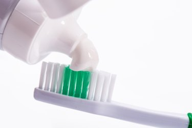 Close-Up Of Toothbrush With Toothpaste Against White Background