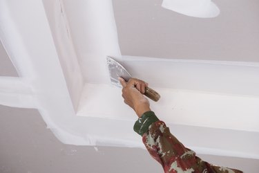 hand of worker using gypsum plaster ceiling joints