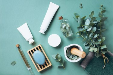 White cosmetic bottles, eucalyptus flowers, towels, soap on green background. Top view, flat lay. Natural organic beauty product concept. Spa, skin care, body treatment