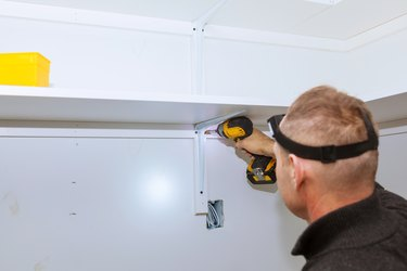 Profile view of a good-looking handyman making some drill wall installing a shelf