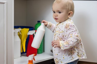 Little girl playing with household cleaners