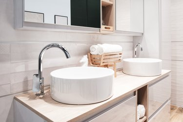 Two luxury faucet mixer on a round bowl white sink in a beautiful beige gray bathroom