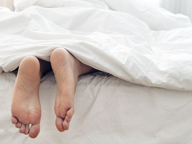 Lazy man and his feet ,  lying  on comfortable bed