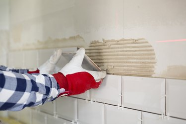 Process of tiling the tiles in the kitchen with necessary tiling tools. Home improvement, renovation concept