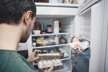 Man holding egg carton by refrigerator in kitchen