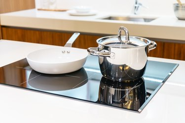 Close-up of stainless steel cooking pot and pan on induction hob in modern kitchen. modern kitchen pot cooking induction electrical stove hob concept