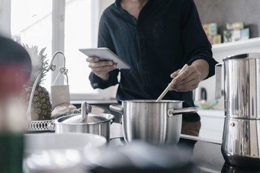 Man standing in kitchen reading news on his digital tablet while cooking