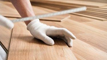 Installing laminated floor, detail on man hands in white gloves, holding measuring tape over wooden tiles