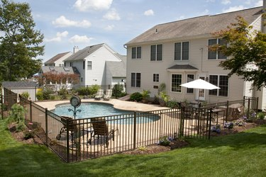 Lush backyard pool and patio behind colonial style home.