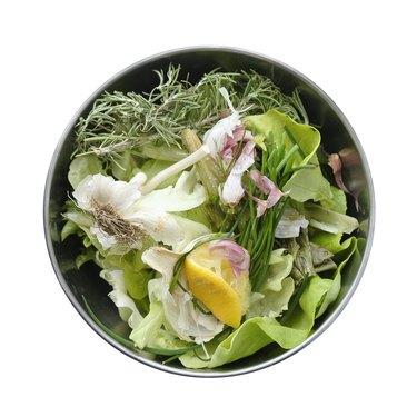 A bowl of kitchen waste, organic garbage (vegetables, herbs)