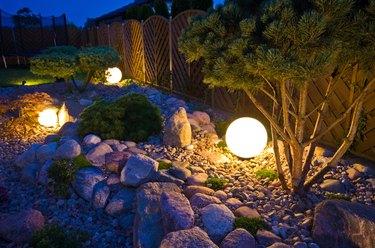 Home garden at night, illuminated by globe shaped lights