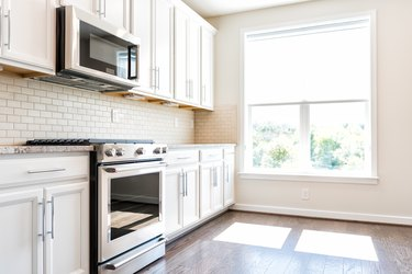 Modern gray, brown neutral kitchen features front cabinets with granite countertops and tile backsplash, window in contemporary home, house, apartment