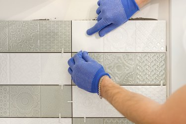 Installing ceramic tiles on the wall in kitchen. Placing tile spacers with hands, renovation, repair, construction