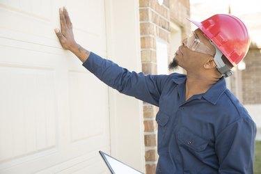 Home inspector examines recent construction using digital tablet.