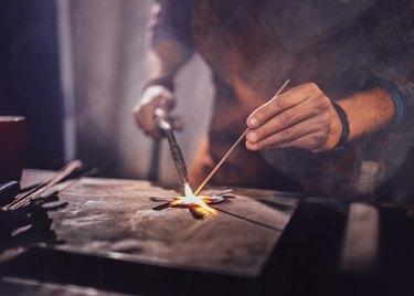 Professional mechanic soldering metal in workshop garage