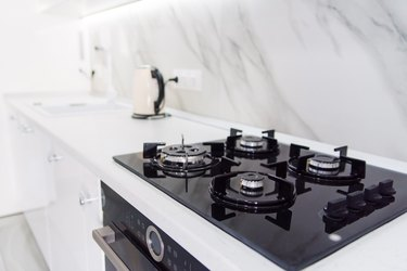 Modern high-tech black gas stove with sensor panel in the bright interior of the kitchen