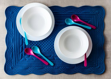 A set of baby dishes on a blue soft napkin for breakfast. kitchen table accessories for serving. Colored small spoons.