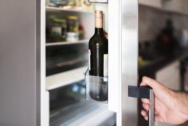 Cropped Hand Holding Refrigerator Door