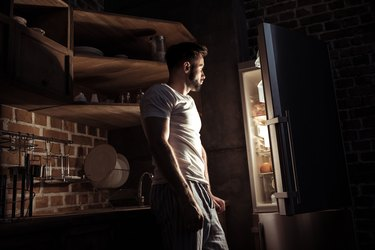 side view of bearded young man in pajamas looking at open refrigerator at night