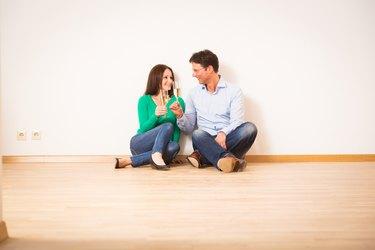 Couple sitting on hardwood floor.