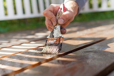 Hand holding a brush applying varnish paint on wooden surface