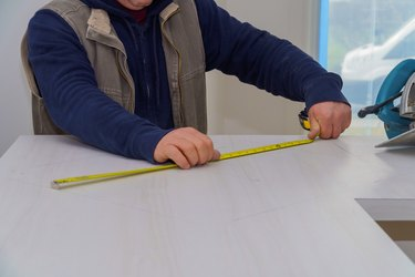 Contractor a laminate kitchen formica counter top. Focus on saw.