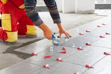 Ceramic Tiles. Tiler placing ceramic wall tile in position over adhesive with lash tile leveling system