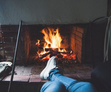 Low Section Of Person By Fireplace At Home