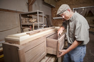 Carpenter uses chisel (tool) on cabinet drawer