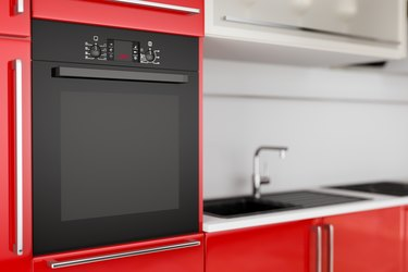 Modern Black Electric Oven Build In Red Kitchen Furniture. 3d Rendering