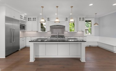 Beautiful kitchen in new luxury home with large island, pendant lights, and hardwood floors. Shows large stainless steel refrigerator.
