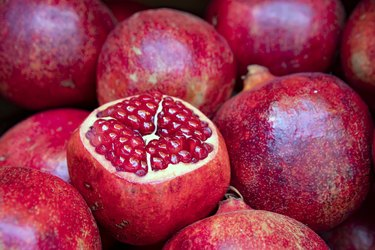 Open fruit of ripe pomegranate with burgundy grains close-up in a pile of pomegranates