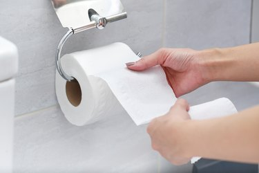 Midsection Of Woman Holding Tissue Paper In Bathroom