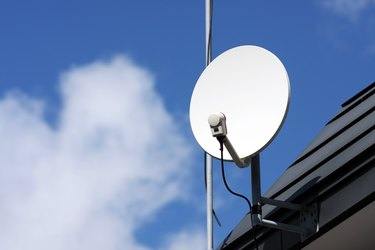 Close-up of a white satellite receiver dish on the roof