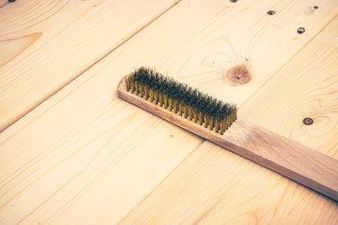 wire brush on wooden plank
