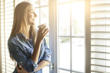Young woman drinking coffee and looking through window