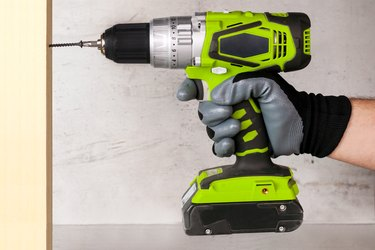 The builder holds in his hand an electric screwdriver on the background of a concrete wall. Screws screw into a wooden beam. DIY
