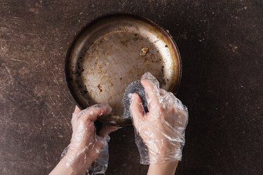Wash the frying pan on a dark marble background. Hygiene. Wash dishes with gloves