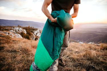 Sleeping bag being rolled up.