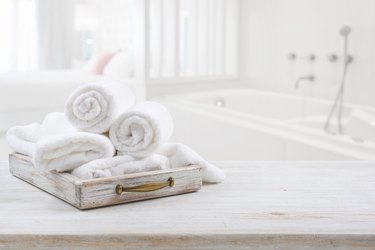 Vintage drawer with white towels over blurred bathroom and bedroom
