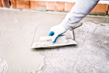 construction worker using trowel and mason's float for waterproofing house