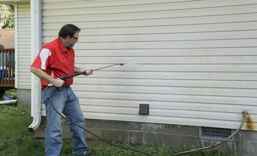 Contractor Using A Pressure Washer To Clean Vinyl Siding