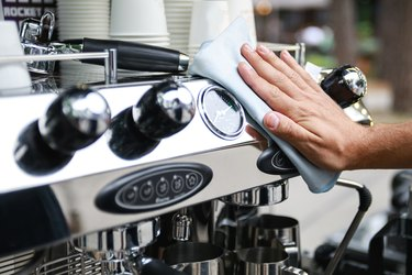Man cleaning espresso machine after working day