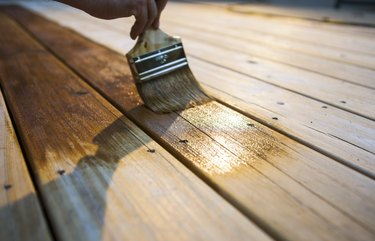Male Carpenter Applying Varnish To Wooden Deck