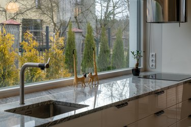 Detail of elegant kitchen furniture with decorative sculptures of cats near the window