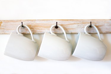 White Cups Hanging on Hooks, White Background, Copy Space